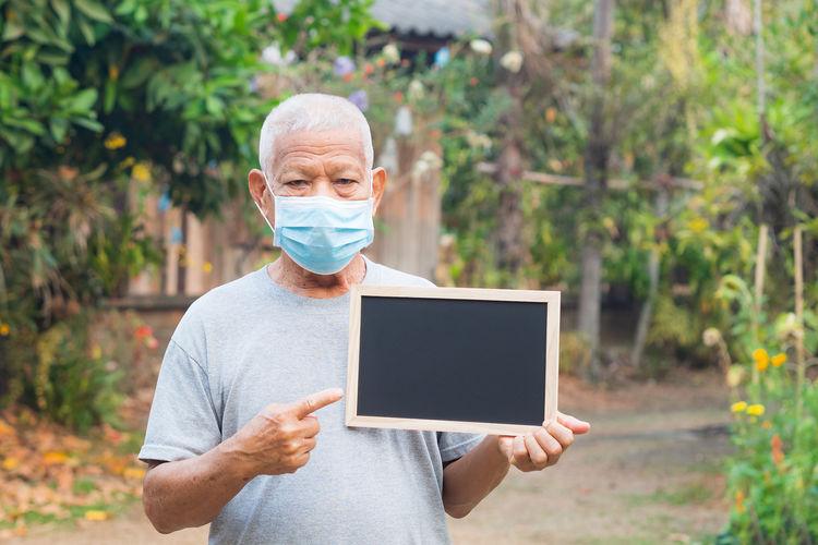 Elderly man wearing mask and holding a blackboard standing in a garden.
