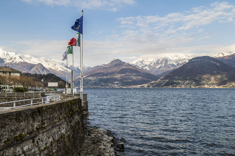 The port of colico with the waving flags of italy and europe with the snow capped alps