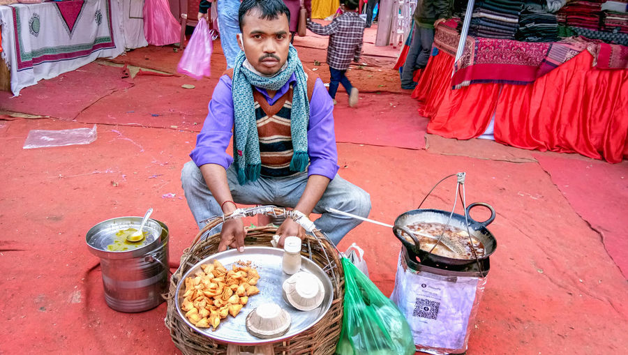 Full length of man sitting at street market