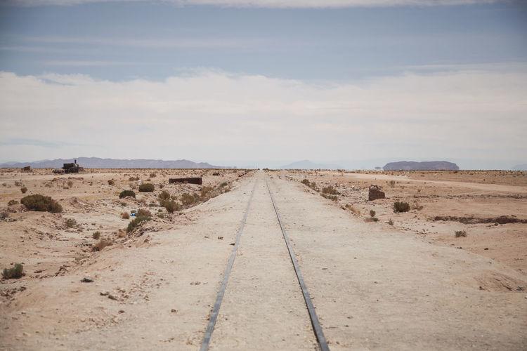 Railroad track in desert against cloudy sky