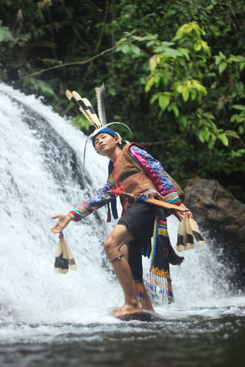 Side view of young man wearing traditional clothing standing against waterfall in forest