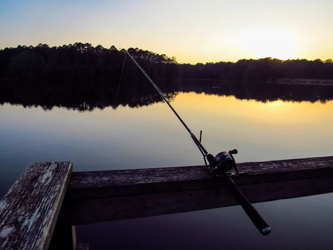 Fishing Pole Rod And Reel Fishing Silhouette Water Reflection Nautical Vessel Fisherman Tranquility Lake Outdoors Nature Sunset Sky Day People Relaxing Moments Nature Lover Water Activity Fishing Pier Dock Travel Catch And Release Outdoor Lover Fishing Dock Going Remote