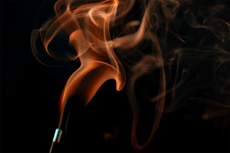 Close-up of smoke from incense stick against black background