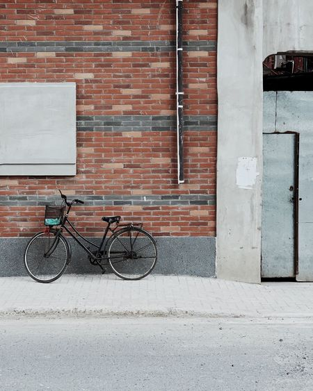 Bicycle on sidewalk against building