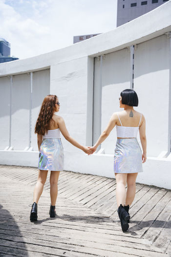 Full length of lesbian couple holding hands while walking outdoors
