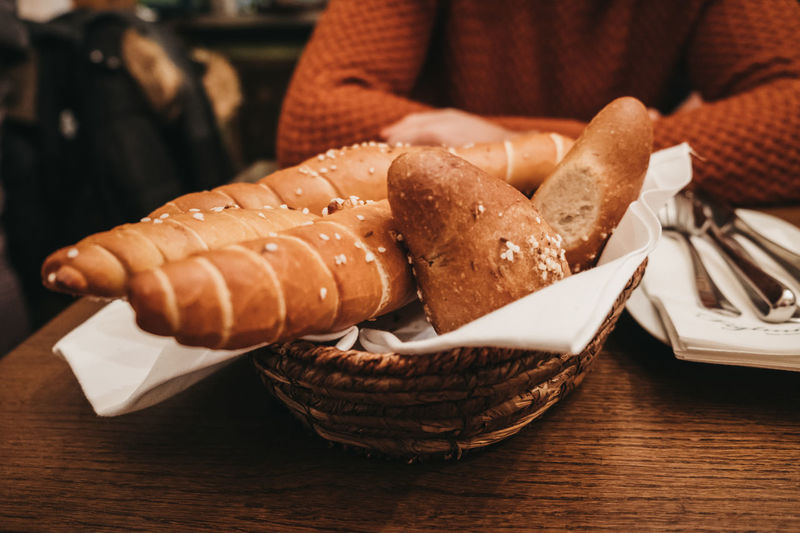 Midsection of woman sitting by breads in wicker basket on table
