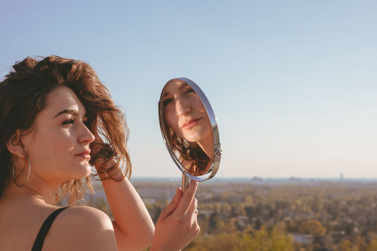 Side view of young woman looking in mirror against clear sky