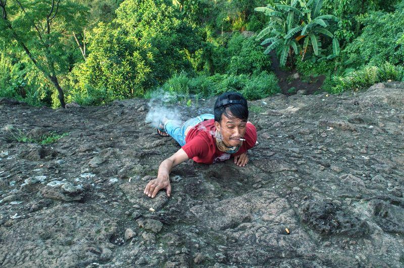 Man smoking cigarette while climbing on rock