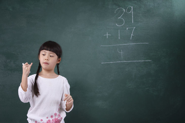 Girl Learning Mathematics On Blackboard