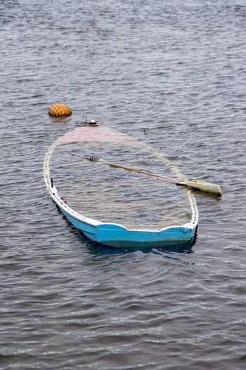 High Angle View Of Abandoned Boat With Oar In Lake