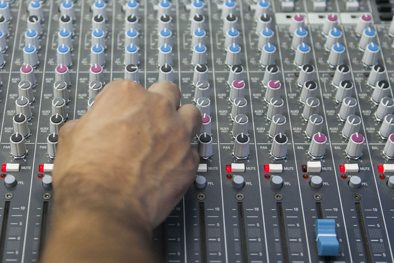 Cropped hand of man mixing music at recording studio