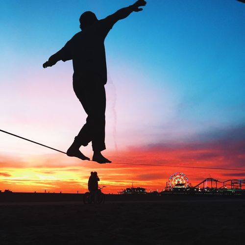Silhouette Man Performing Slackline At Beach Against Sky During Sunset