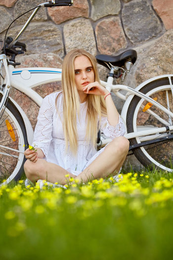 Portrait of beautiful woman with bicycle in background