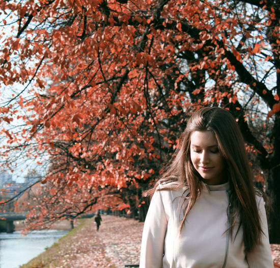 Beautiful young woman standing against autumn trees