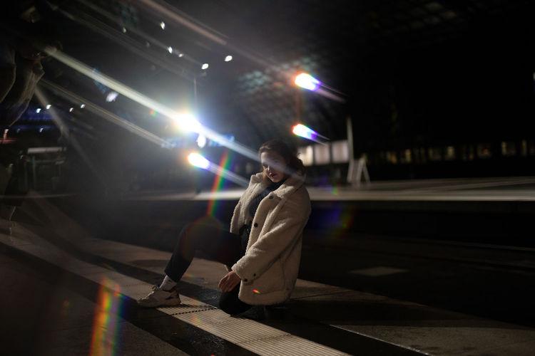 Woman at illuminated bridge during night