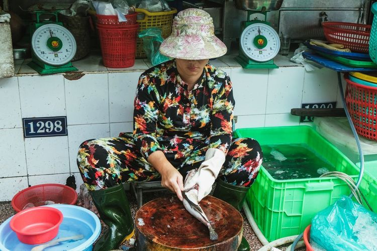 Midsection of woman sitting at market stall