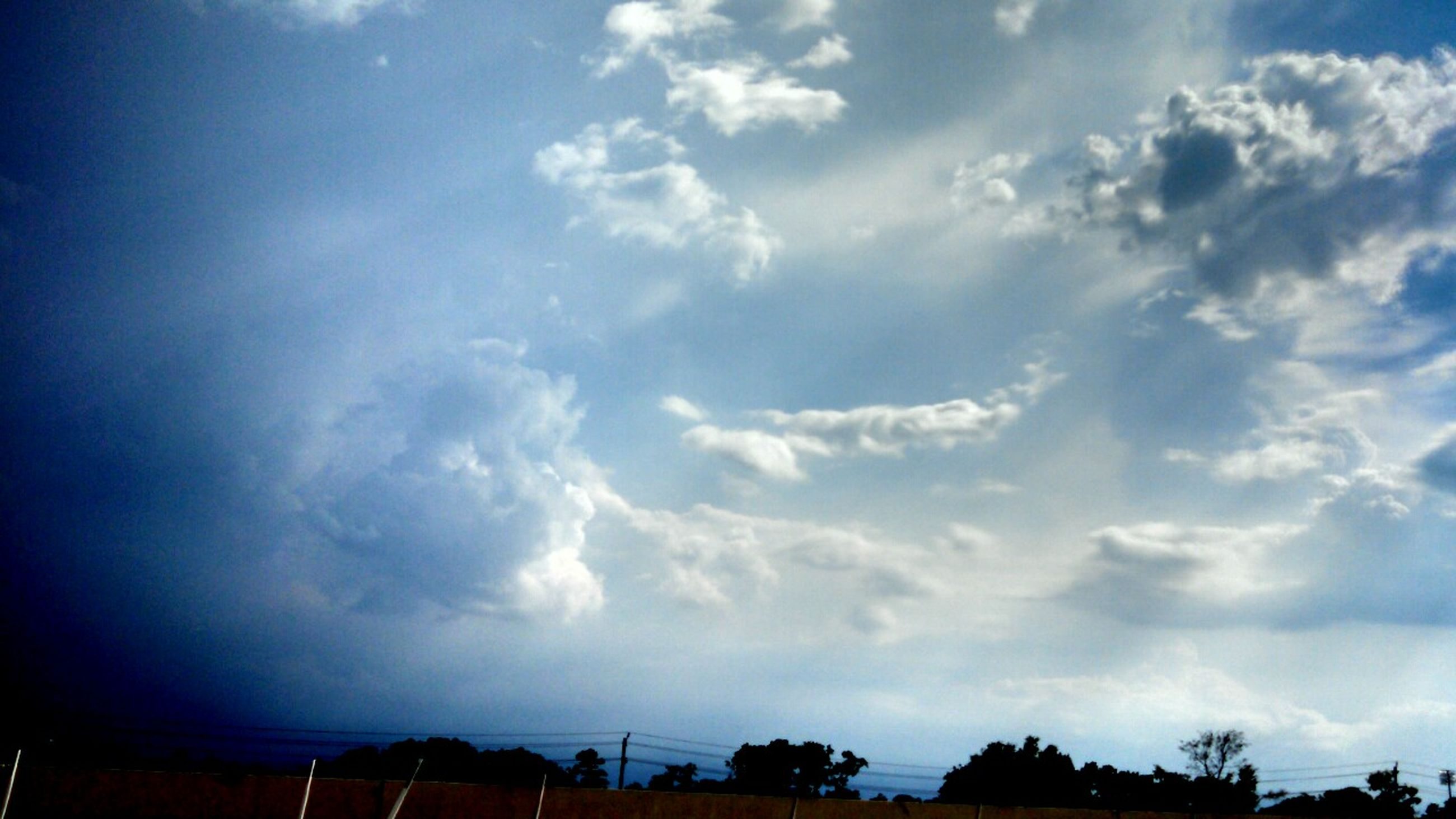 sky, cloud - sky, low angle view, blue, cloud, cloudy, built structure, beauty in nature, nature, building exterior, scenics, tranquility, silhouette, architecture, sunlight, outdoors, tranquil scene, no people, tree, day