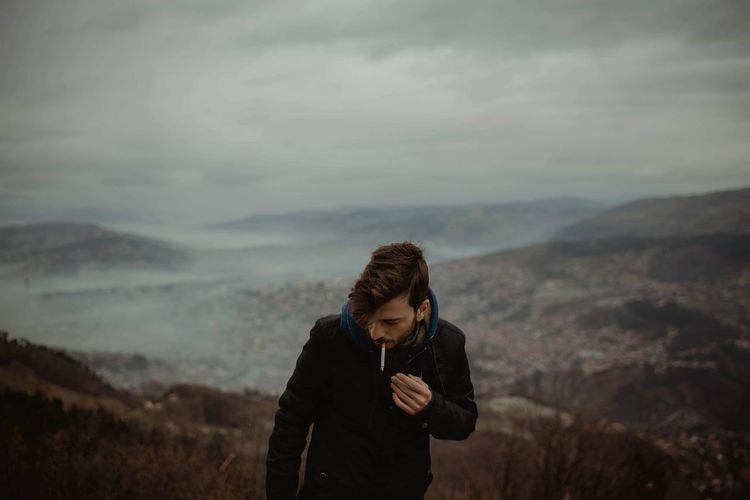 Man smoking cigarette while standing on mountain against sky