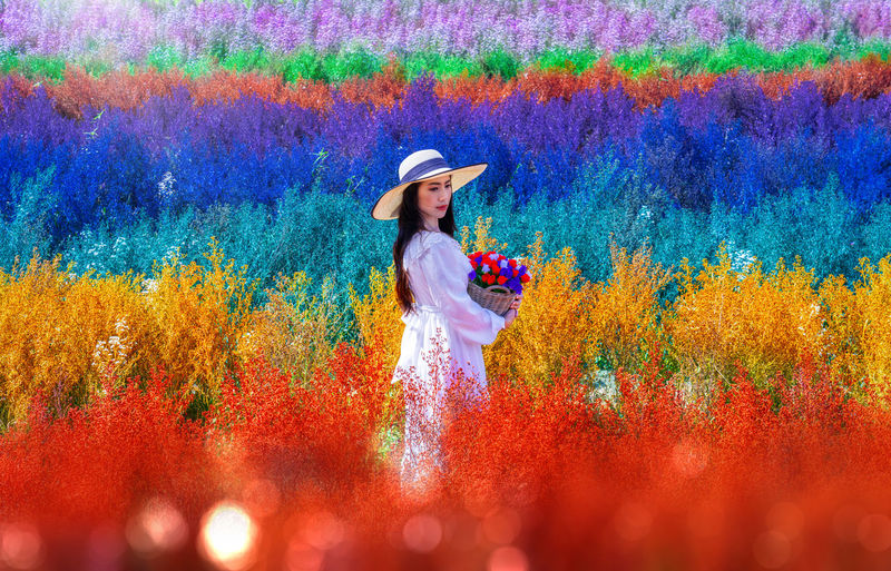 Full length of woman standing by multi colored flower in field