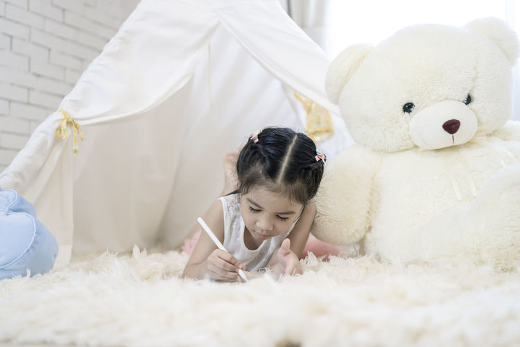 Cute girl with toy on rug at home