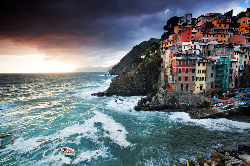 Scenic view of sea by cinque terre against cloudy sky at sunset