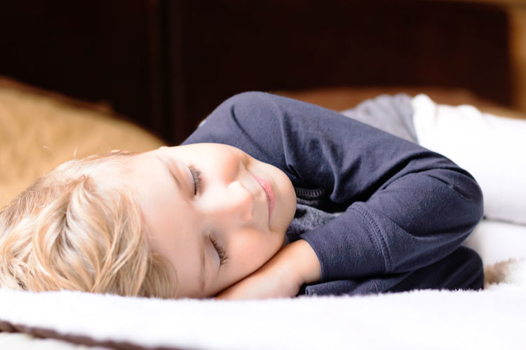Portrait of baby boy sleeping on bed at home