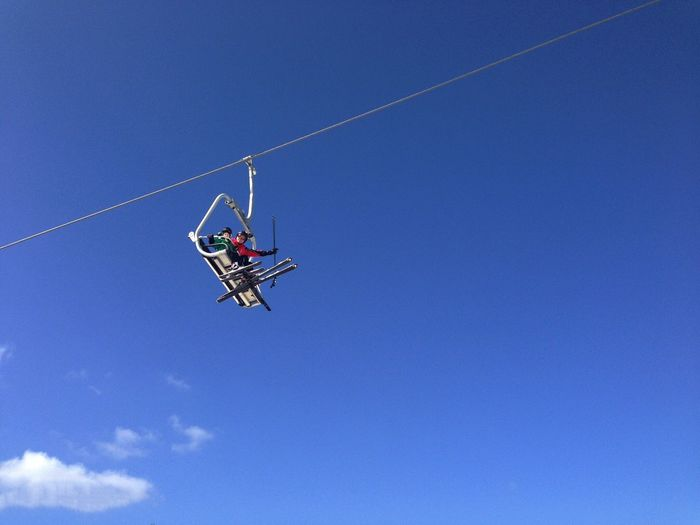 Low Angle View Of People In Ski Lift Against Sky