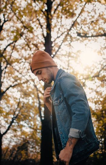 Low angle view of man standing by tree autumn warm