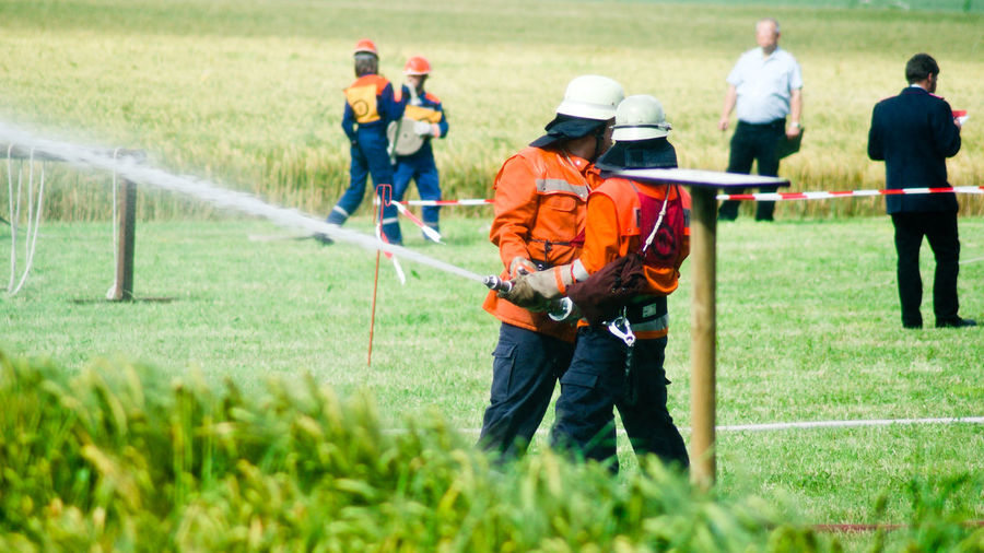 Firefighters Spraying Water From Hose While Standing On Grass Field