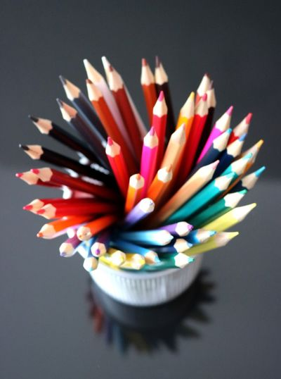 Close-up of multi colored pencils on table in case on table
