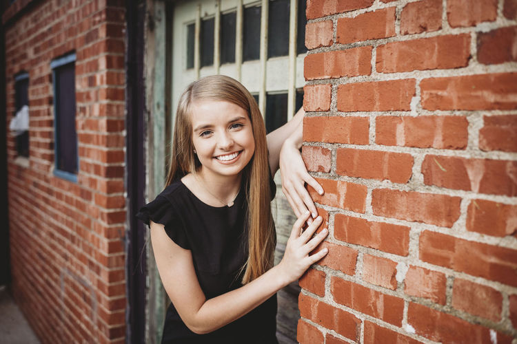 Portrait of smiling woman standing by brick wall