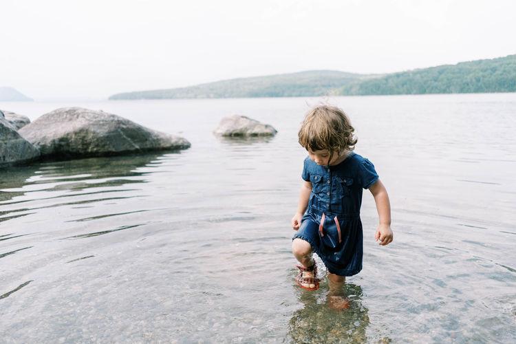 Rear view of boy in water against sky