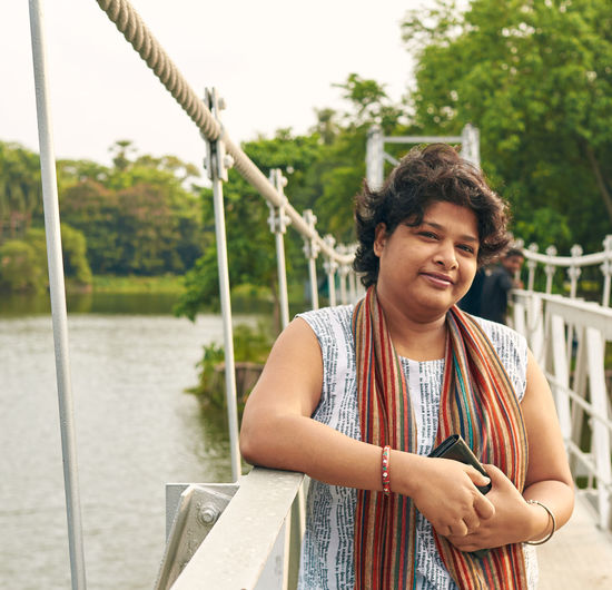 A bengali woman standing on the hanging bridge at rabindra sarovar lake, kolkata