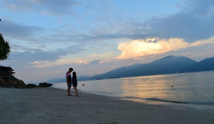 """==괜찮아== It is 7am morning Sunrise look like sunset? ken cya na... Sun hide in the cloud? ken cya na... High cant reach to me? ken cya na... U are the only one in my eye, everything other than that also ken cya na... Ken cya na mean """"nevermind"""" by the way... =) Two People Beach Full Length Outdoors People Togetherness Vacations Nature Adult Kencyana 괜찮 Cloud Love Sky Day Island Pangkor Malaysia Dramatic Sky Nature First Eyeem Photo No People Love"""