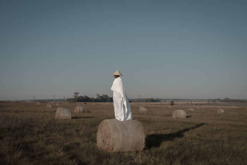 Young man covered with fabric standing on hay bale at agricultural landscape
