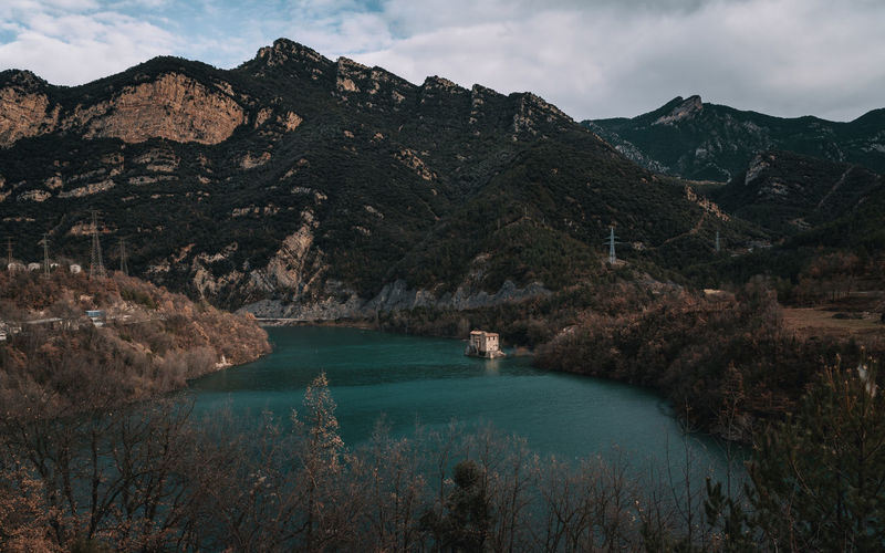 Scenic view of lonely house by lake and mountains against sky