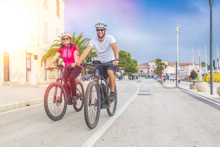 Couple Riding Bicycles On Road In City