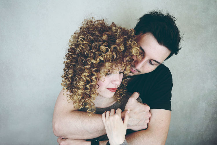 Couple Embracing Against Wall