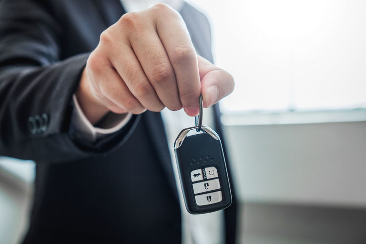 Midsection of insurance agent holding car key