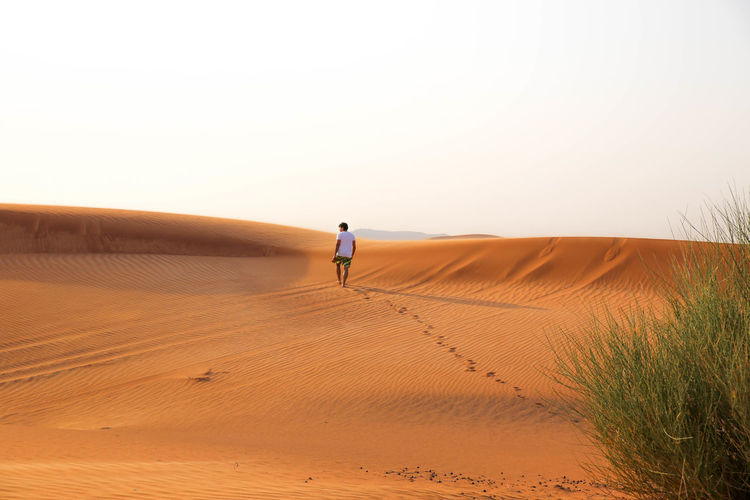 Man walking on sand dune
