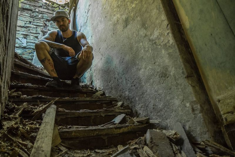 Low angle view of man crouching on staircase in abandoned building