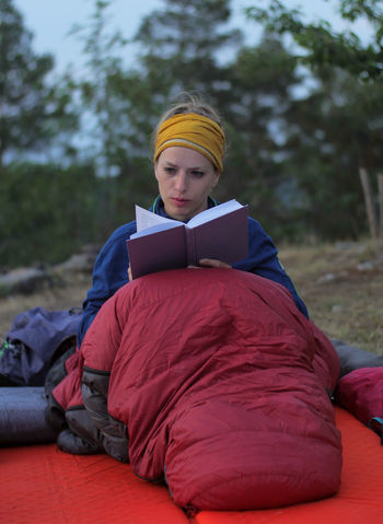young caucasian female reading book while outdoor camping Backpacking Camping Hiking Nature Reading Travel Trekking Woman Book Caucasian Child Clothing Day Education Female Focus On Foreground Front View Full Length Girl Hikingadventures Hobby Land Leisure Activity Lifestyles Males  One Person Outdoors Paper People person Real People Red Relaxation Resting Sitting Teenager Tent Tree Vacation Young Adult