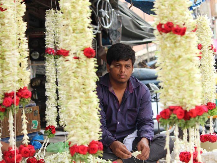 Portrait Of Vendor Selling Floral Garlands At Market