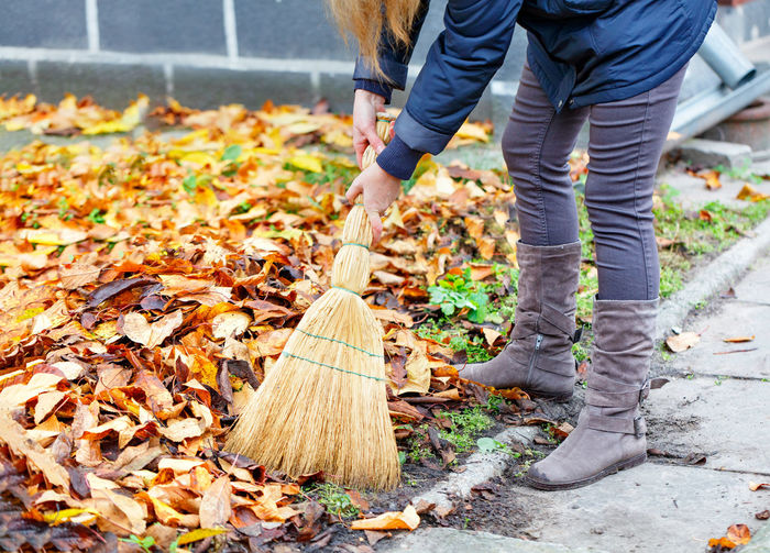 Low section of woman cleaning autumn leaves by sidewalk