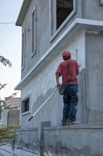 Low Angle View Of Man Painting House