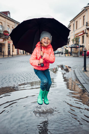 Happy smiling girl holding big umbrella jumping in the puddle during walk in a downtown