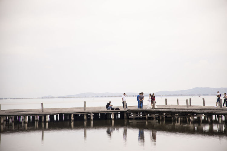 People standing on pier over sea against clear sky