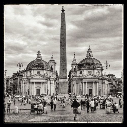 Tourists in front of church against cloudy sky
