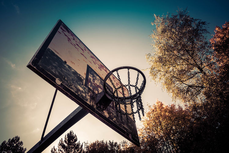 Low angle view of basketball hoop against sky during sunset