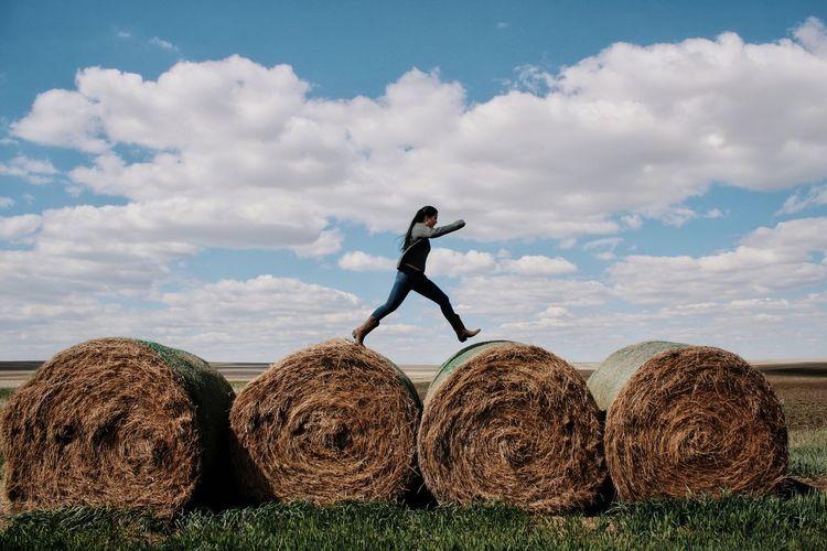 Full frame shot of hay bales on field against sky